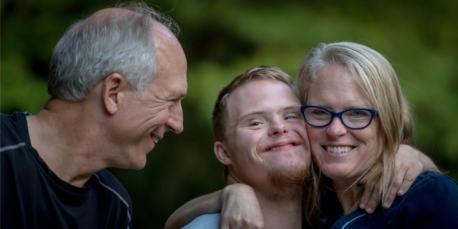 Twee lachende ouders knuffelend met lachende zoon met verstandelijke beperking